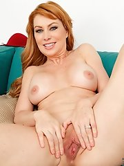 Hot redhead Sasha Sean slowly gets naked and finger fucks her wet pussy on the couch